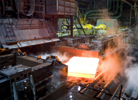 A large glowing piece of metal comes out of a machine. It steams.
