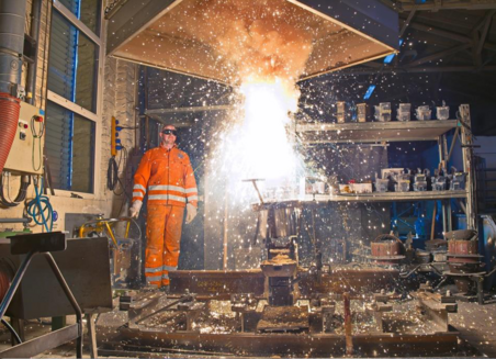 Photo shows a workshop where yellow sparks fly during a chemical reaction. A man in work clothes and protective goggles is standing next to it at some distance.