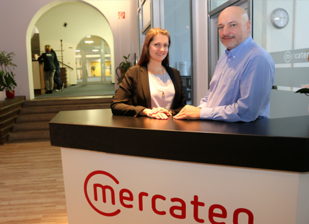 Two Mercateo employees stand behind a counter with the company logo in the company's offices.