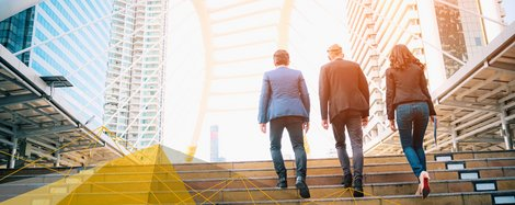 Two men and a woman walk up a staircase between high-rise buildings.