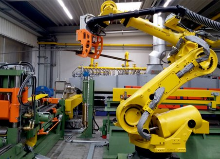 Machine operated robot arm transports a component from one machine to another.